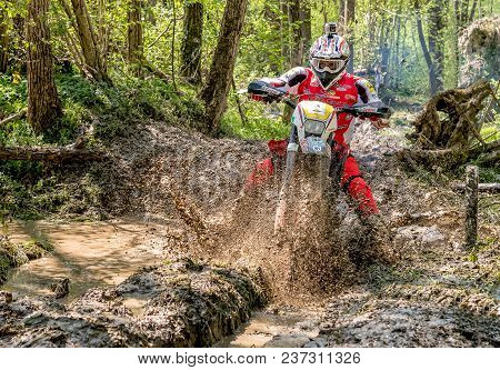 Biandronno, Italy - April 22, 2018: Motocross Rider Splashing Mud On Wet And Muddy Terrain. Open Com