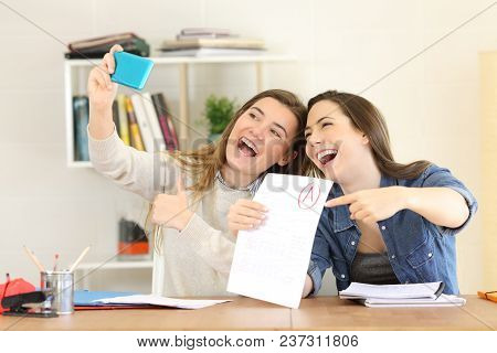 Two Excited Students Celebrating Exam Approval Taking Selfies With A Smart Phone