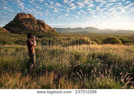 Young Asian Male Photographer Taking Photo Of Beautiful Sunrise In Savanna (savannah) Woodland, Nami
