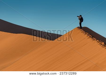 Young Male Traveler And Photographer Standing On The Top Of Sand Dune Photographing Sunrise Or Sunse