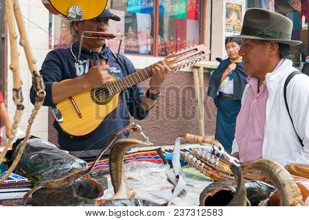 Otavalo April 2018 Playing The Guitar In Artesanal Market Of Otavalo Ecuador, To Attract Customers