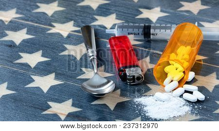 Front View Of Opioid Pain Killer Tablets With Spoon, Lighter And Syringe On Rustic Usa Flag In Backg