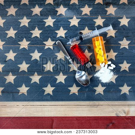 Overhead View Of Opioid Pain Killer Tablets With Spoon, Lighter And Syringe On Rustic Usa Flag In Ba