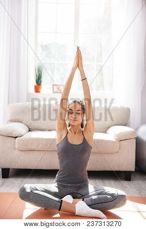 Yoga Makes Happy. Charming Upbeat Woman Sitting In The Lotus Pose And Smiling Pleasantly While Pract