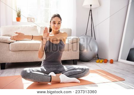 Favorite Pastime. Charming Slim Woman Sitting On The Mat And Practicing Yoga In The Morning While Sm