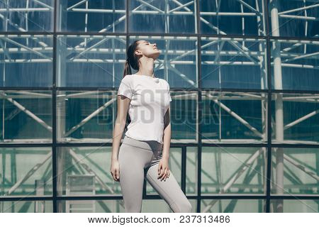 Attractive Athletic Girl Resting Before Training Outdoors In The Sun, Loves Sports And Fitness