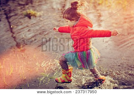 Side View Of Charming Confident Little Girl Walking In Gumboots In Puddle Splashing Water In Sunset