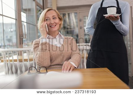 My Coffee. Smiling Aged Woman Talking On The Phone And The Waitress Holding Her Coffee