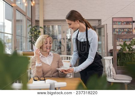 Your Coffee. Adorable Dark-haired Waitress Smiling And Serving Coffee For Her Client