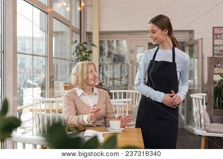 Best Waitress. Exuberant Young Waitress Talking With Her Client And Her Client Drinking Coffee