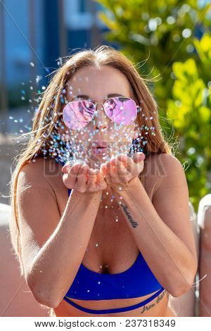 A blonde bikini model blowing glitter during the holiday weekend