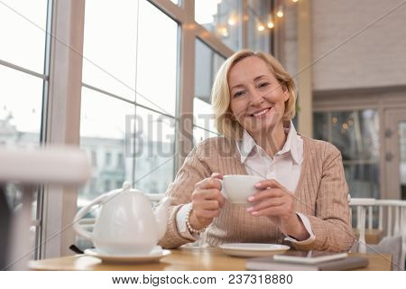 Pleasant Day. Charming Blond Woman Sitting In A Cafe And Drinking Tea