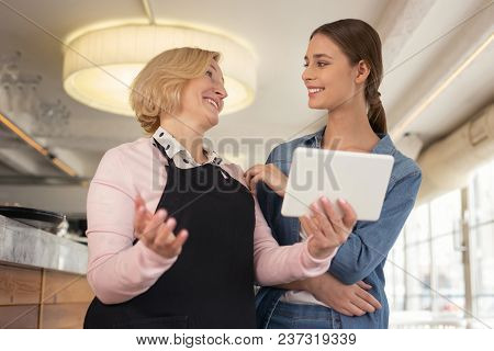 Our New Menu. Smiling Blond Waitress Holding A Tablet And Talking With Her Young Employer