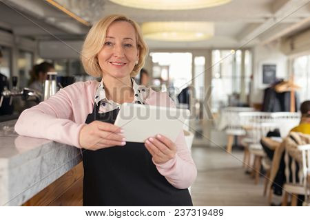 Being A Waitress. Delighted Aged Waitress Holding A Tablet And Smiling