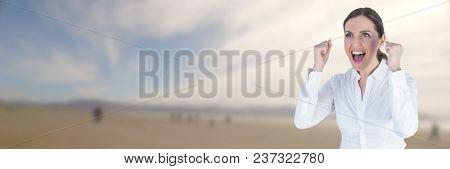 Business woman celebrating on blurry beach