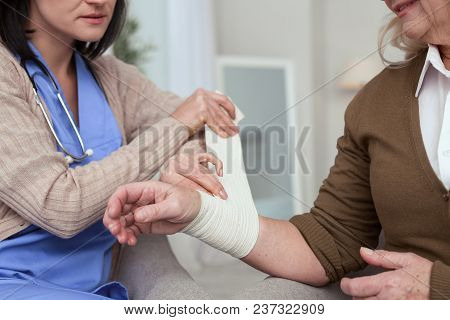 Give Your Hand. Close Up Of Female Hands Bandaging Hand While Taking Care Of Stretching