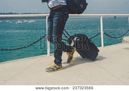 Departing With My Suitcase. Man Walks On A Pier Carrying A Suitcase. Tourist Pulls His Suitcase On W