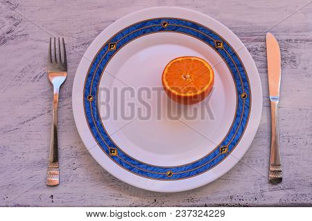 Half An Orange Fruit Served For Eating At A Plate At Light Wooden Background/ Conceptual Image Of Di