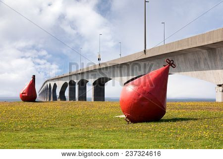 Giant red metal buoys on the grass infront of the eight mile long Confederation Bridge, that links Prince Edward Island with New Brunswick, Canada.