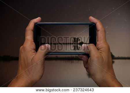 Man Hand Holding And Using Mobile,cell Phone,smart Phone Photography And Lake In The Night With The