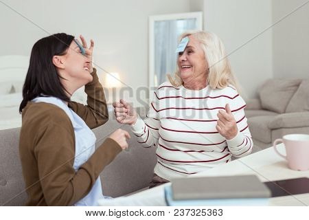 Excellent Game. Vigorous Elder Woman And Caregiver Talking While Playing Game