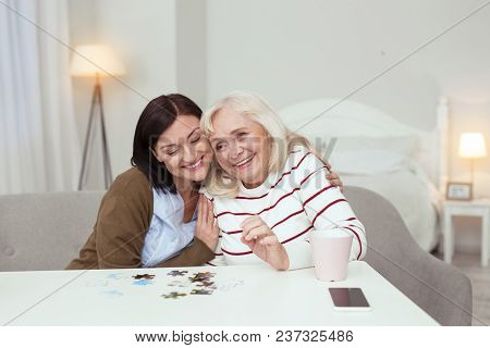 Interesting Puzzle. Cheerful Elder Woman And Caregiver Hugging While Gathering Puzzle