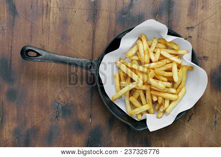 French Fries Served In Frying Pan On Wooden Table, Top View