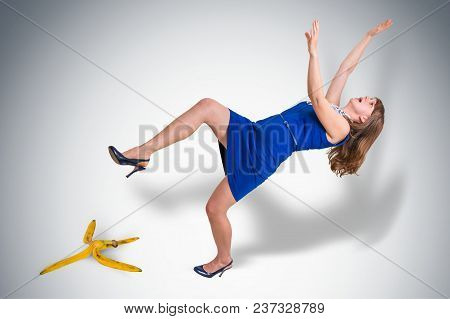 Business Woman Slipping And Falling From A Banana Peel - Business Risk Concept