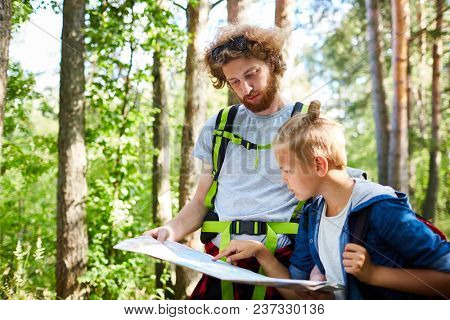 One of boy scouts with backpacks pointing at map while looking for dwelling area in the forest