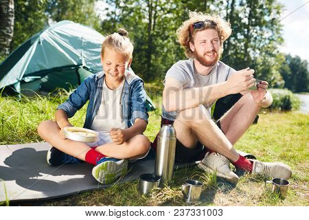 Two young trippers sitting on ground in natural environment and having breakfast in the morning