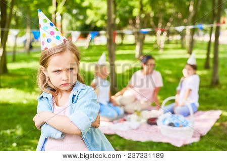Offended littlee child hugging herself and scowling on background of other people enjoying picnic in park on summer day