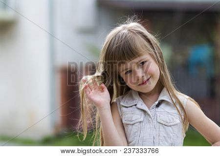 Portrait Of A Pretty Little Long-haired Blond Child Girl In Sleeveless White Dress Smiling Shyly Int