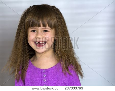 Portrait Of Happy Smiling Little Girl With Beautiful Thick Hair