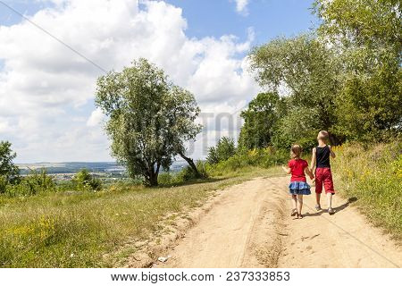 A Boy And A Girl Children Walk On A Dirt Road On A Sunny Summer Day. Kids Holding Hands Together Whi