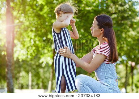 Little girl crying while mother comforting her during promenade in park on summer day