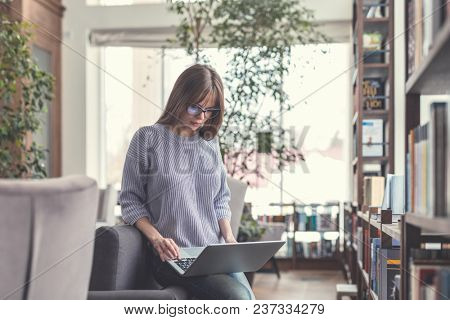Young woman with laptop in the library