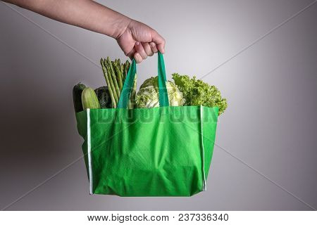 Close Up Hand Holding Green Grocery Bag Of Mixed Organic Green Vegetables , Healthy Organic Green Fo