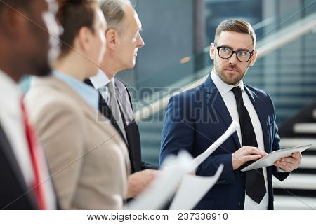 Serious broker in suit and eyeglasses looking at his colleagues during training at business briefing while presenting and explaining them some important information