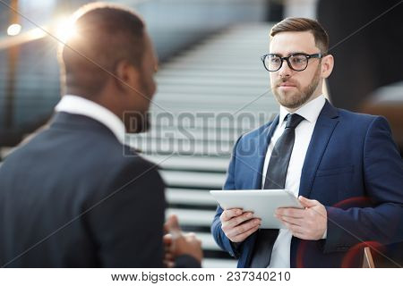Young elegant trader in formalwear looking at his African-american colleague during discussion of business information at meeting in lounge