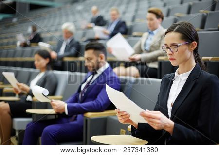 Young serious businesswoman and other people in formalwear reading papers in auditorium or conference hall