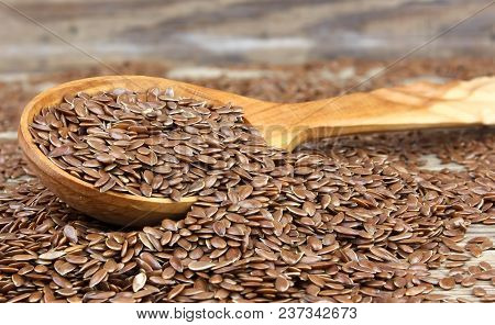 Flax Seeds In Wooden Spoon On Wooden Background.  Also Known As Linseed, Flaxseed And Common Flax. P