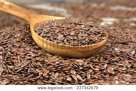 Flax Seeds Scattered Grains On Wooden Background With Wooden Spoon. Also Known As Linseed, Flaxseed