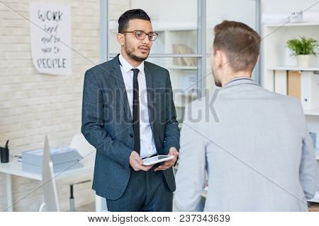 Handsome Mixed-race Manager In Eyeglasses Analyzing Results Of Accomplished Work With Male Colleague