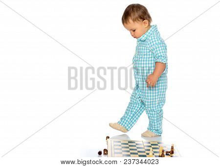 Little Boy Is Playing Chess On A White Background. The Concept Of A Happy Childhood, The Harmonious