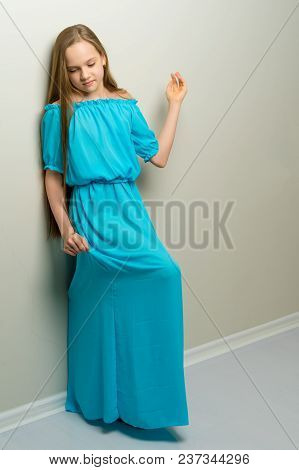 A Charming School-age Girl Leaned Back Against The Wall In The Studio. The Concept Of Happy People,