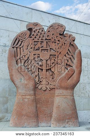 Yerevan, Armenia - October 05, 2017: Sculptural Composition Of Hands With Coat Of Arms