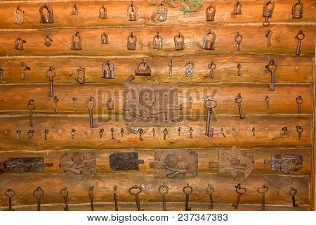 A Collection Of Old Keys And Locks On A Wooden Log Wall.