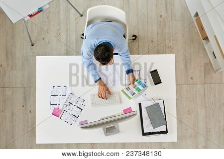 Directly Above View Of Creative Interior Designer Sitting At Desk And Working On Ambitious Project,