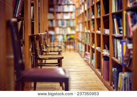 Library with rows of books on shelves and empty chairs