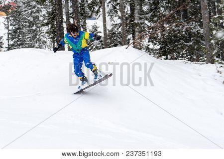 Vintage Photo Of Young Man Snowboarder Jumping In The Mountains, Retro Style 1980 Concept.